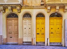 The densely located doors, Valletta, Malta. The beautiful densely located narrow doors, decorated with carved reliefs and grills, South street, Valletta, Malta Stock Photos