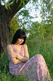 Beautiful depressed girl sitting alone on summer meadow. Beautiful sad girl sitting alone on the meadow on sunny summer day royalty free stock photography