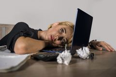 Beautiful depressed sad blonde woman working with laptop computer feeling tired sitting at office desk overwhelmed by paperwork su. Young beautiful depressed and stock photography