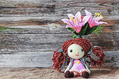 Beautiful designed doll with plastic flowers. On the wooden background Royalty Free Stock Images