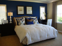 Beautiful Designer Bedroom. With royal blue walls and white comforter Royalty Free Stock Photos