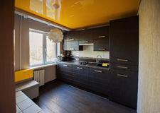 Beautiful designer kitchen in brown and yellow colors Stock Images