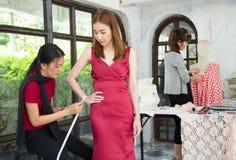 Beautiful designer is working in dressmaking studio measurement Stock Photos