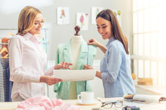 Beautiful designers working. Beautiful young designers are using measure tape and mannequin, discussing sketch and smiling while working in dressmaking studio Royalty Free Stock Photos