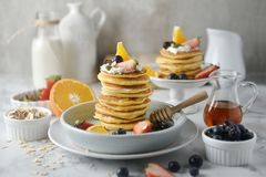 Beautiful dessert, fresh pancakes with blueberries, strawberries, orange, honey and whipping cream on plate. royalty free stock photography
