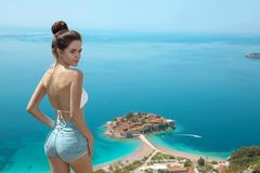 Beautiful destination. Tourist girl sightseeing Sveti Stefan isl. And in Budva, Montenegro. brunette traveller visiting Adriatic Sea, Balkans. Summer travel stock photo