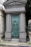 Beautiful detail in family tomb, Pere LaChaise Cemetery, Paris, France, 2016. Beautiful stone and copper family tomb, with large angel guarding the doorway, Pere royalty free stock photography