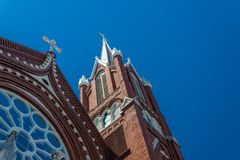 Beautiful details of steeples and rose window, Gothic Revival church, red brick white crosses, blue sky. Horizontal aspect stock image