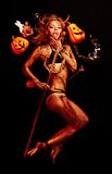 Beautiful devil with trident. And Halloween accessories on black royalty free stock photo
