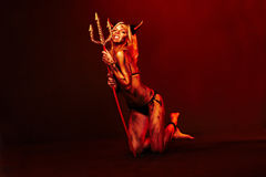 Beautiful devil with trident on deep red Stock Photos