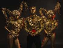 Beautiful devil women with golden ornamental horns and handsome devil man in ornamental jacket. Beautiful devil women with golden ornamental horns and handsome Stock Images