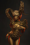 Beautiful devil women with golden ornamental horns. Beautiful devil woman with golden ornamental horns on dark background Royalty Free Stock Photo