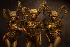Beautiful devil women with golden ornamental horns. Beautiful devil woman with golden ornamental horns on dark background Royalty Free Stock Photos