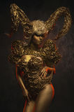 Beautiful devil women with golden ornamental horns. Beautiful devil woman with golden ornamental horns on dark background Stock Image