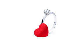 Beautiful diamond ring and a red felt heart on white background Royalty Free Stock Photo