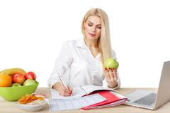 Dietician making a diet of fruits and vegetables. Beautiful dietician woman making a diet plan and looking at apple royalty free stock photography