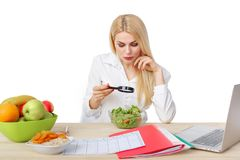 Dietician making a diet of fruits and vegetables. Beautiful dietician woman making a diet plan and looking in magnifier on salad for proper nutrition stock images