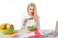 Dietician making a diet of fruits and vegetables. Beautiful dietician woman making a diet plan and looking in magnifier on salad for proper nutrition stock photos