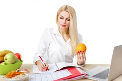 Dietician making a diet of fruits and vegetables. Beautiful dietician woman making a diet plan and looking at orange royalty free stock photos