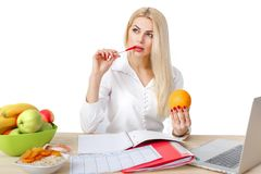 Dietician making a diet of fruits and vegetables. Beautiful dietician woman making a diet plan and looking at orange stock images