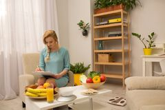 Female doctor dietitian. Beautiful dietitian sitting in arm chair in office. Making a diet for patient Stock Images