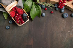 Beautiful different berries with leaves in a basket on a wooden table, top view with copy space for text. Beautiful different berries with leaves blueberries Stock Image