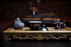 Beautiful dishes for a tea ceremony close-up on a wooden board with statues stock photo
