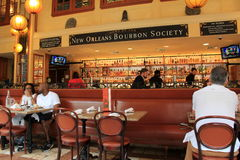 Beautiful display of bourbons in glass and wood cases, with guests at tables, seen in Bourbon House Restaurant, New Orleans, 2016 Royalty Free Stock Photo