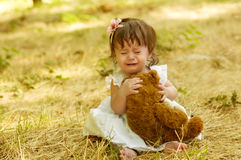 Beautiful dissatisfied baby girl on a field Stock Image
