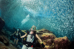 Beautiful diver in fish and corals reef background Royalty Free Stock Photography