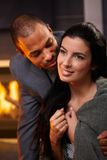 Beautiful diverse couple at home smiling. Beautiful diverse couple embracing at home by fireplace, smiling royalty free stock photo