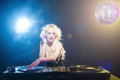 Beautiful DJ girl on decks in the disco.  Stock Photography