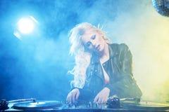 Beautiful DJ girl on decks in the disco.  Stock Photos