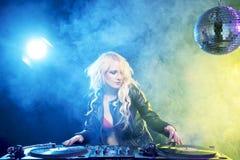 Beautiful DJ girl on decks in the disco.  Stock Images