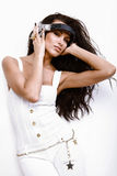 Beautiful dj woman with long black hair in white. Coveralls poses holding earphones on white background Royalty Free Stock Photos
