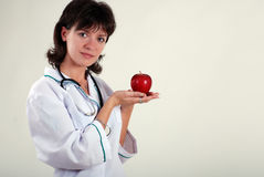 Beautiful doctor with apple Stock Photos