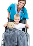 Beautiful doctor carrying adorable little boy. Beautiful female doctor carrying adorable little boy in the wheelchair at the hospital Royalty Free Stock Photography