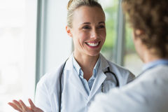 Beautiful doctor discussing with colleague Stock Images