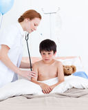Beautiful doctor examining a little boy Royalty Free Stock Photo