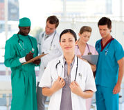 Beautiful doctor with her team in the background royalty free stock photo