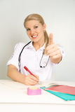 Beautiful doctor with her thumb up Stock Images