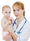 Beautiful doctor holding a cute baby in her arms royalty free stock photography