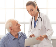 Beautiful doctor and patient. Beautiful female doctor in white medical coat is consulting her handsome old patient and using a digital tablet Stock Images