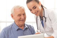 Beautiful doctor and patient. Beautiful female doctor in white medical coat is consulting her handsome old patient, using a digital tablet and smiling Stock Image