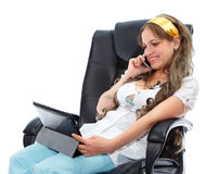 Beautiful doctor sitting in armchair and speaking on the phone Royalty Free Stock Photos