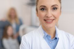 Beautiful doctor is standing against blurred background stock images