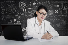 Beautiful doctor write prescription at lab Royalty Free Stock Photography