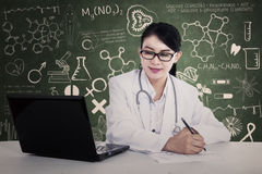 Beautiful doctor writes formula Royalty Free Stock Image