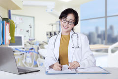 Beautiful doctor writes prescription on table Stock Images