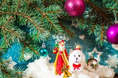 Beautiful dog holding a gift box in mouth by the ribbon for Christmas. Christmas background for notebook diary cover - Christmas tree Santa Claus and dog toy New Royalty Free Stock Images